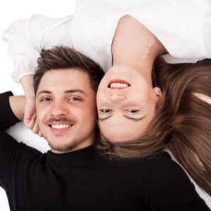 52668865 - happy young couple lying down on their back together